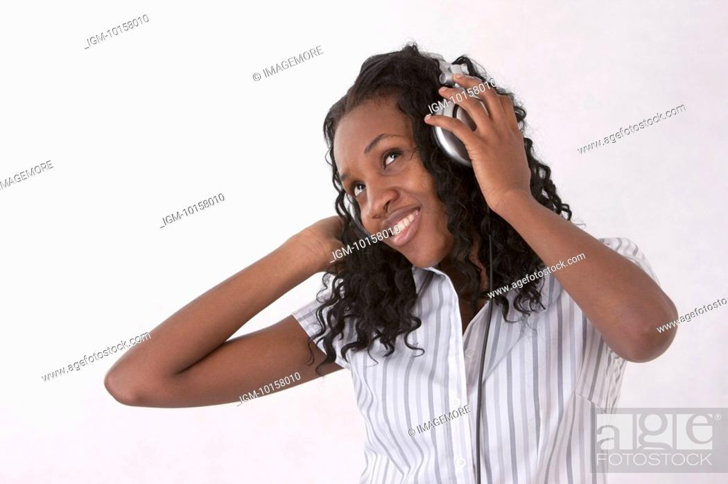 Stock Photo: Young woman looking up with smile and listening music with headset.
