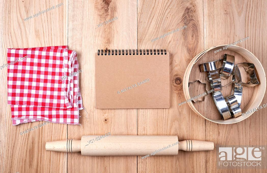 Imagen: open notebook in a cell, round wooden sieve with baking molds, top view.