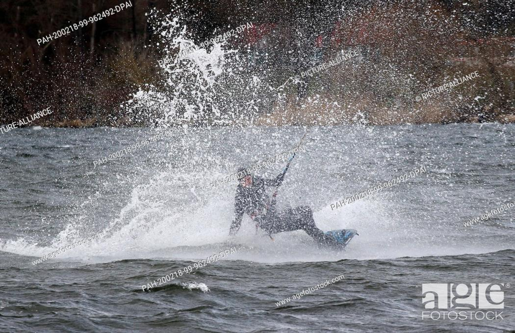 Stock Photo: 18 February 2020, Berlin: At wind speeds of up to 59 km/h and temperatures of around seven degrees Celsius, a kitesurfer moves over the churning water of Lake.
