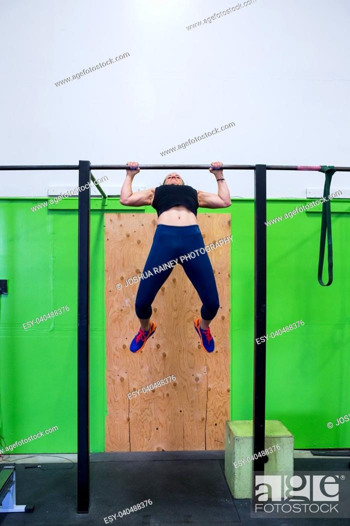 Stock Photo: Fit woman doing exercises and pullups on a pullup bar at a crossfit gym for females.