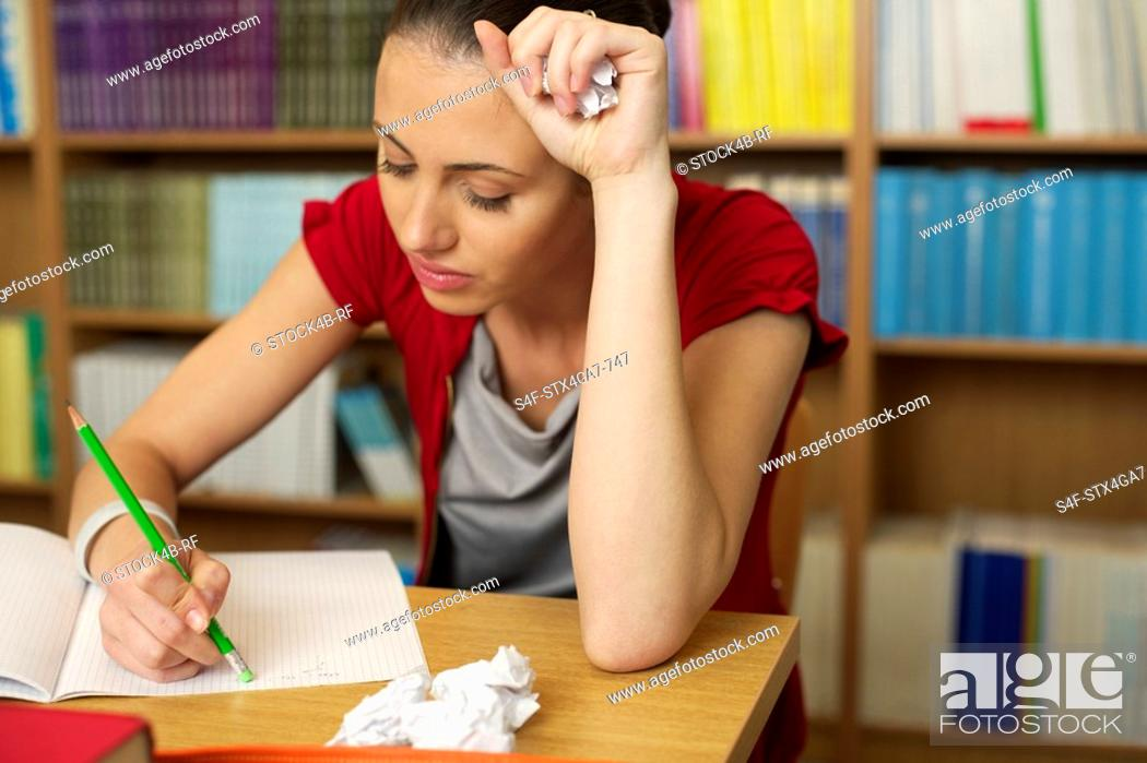 Stock Photo: Female student working in a library.