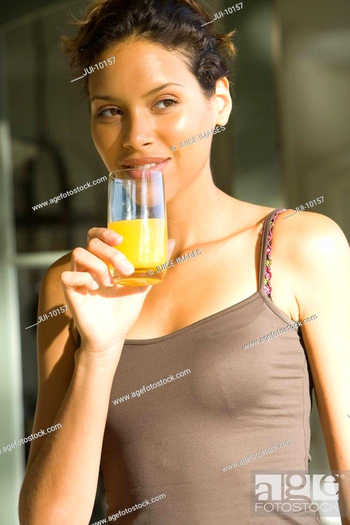 Stock Photo: Young woman drinking orange juice, close-up.