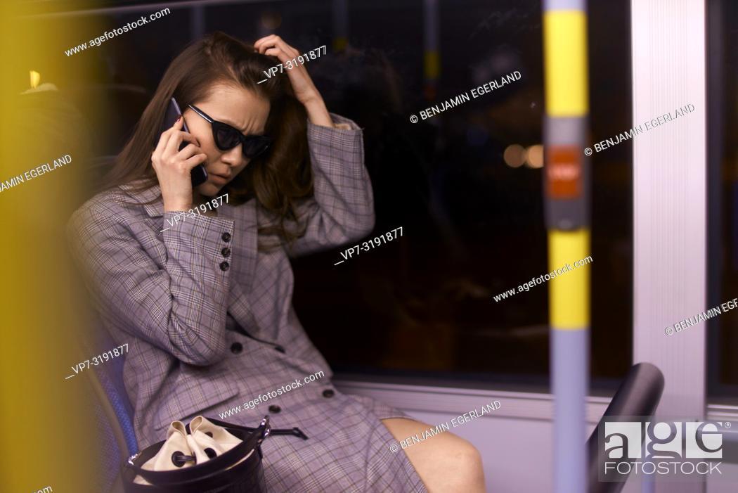 Imagen: Woman in tram by night, talking by phone. Munich, Germany.