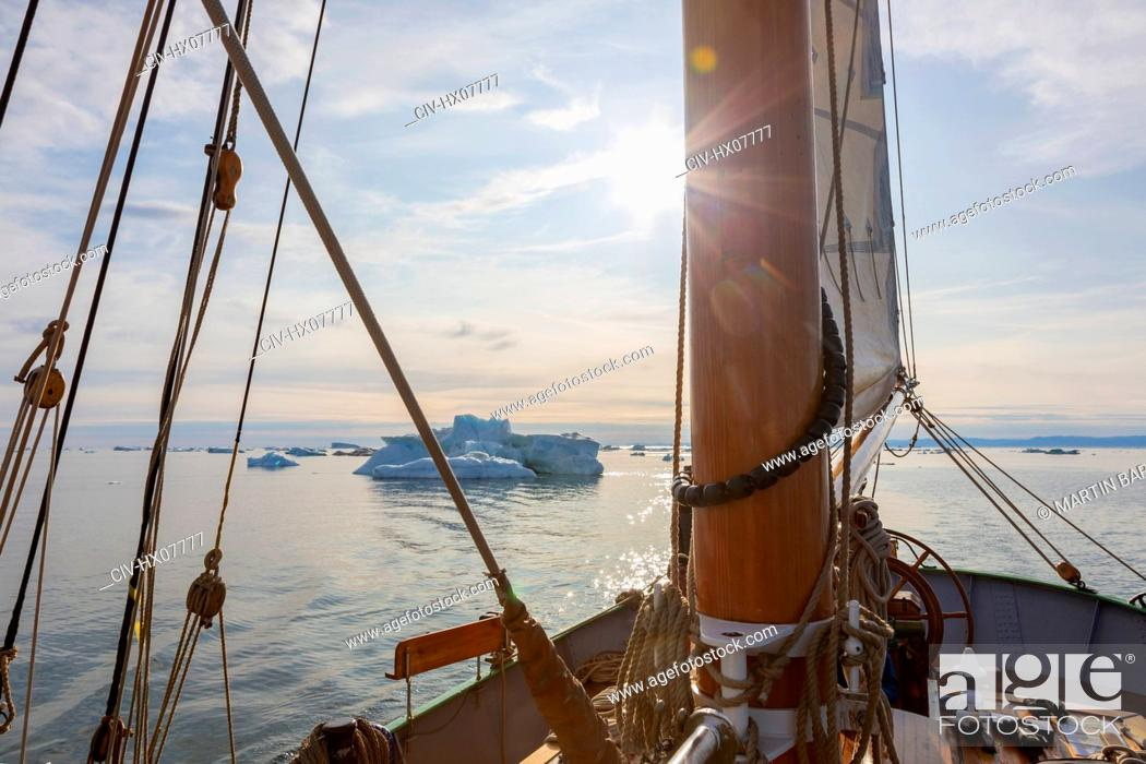 Stock Photo: Ship sailing toward icebergs on sunny tranquil Atlantic Ocean Greenland.