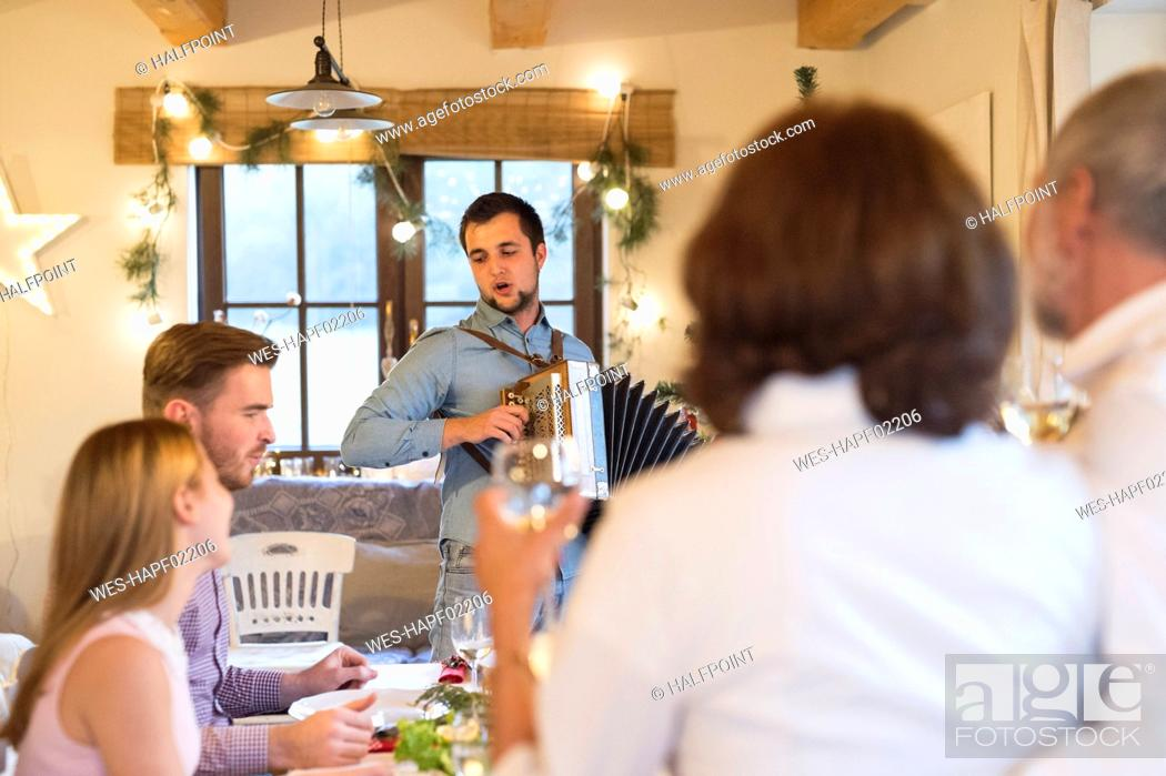 Stock Photo: Young man playing accordion for family at Christmas dinner table.