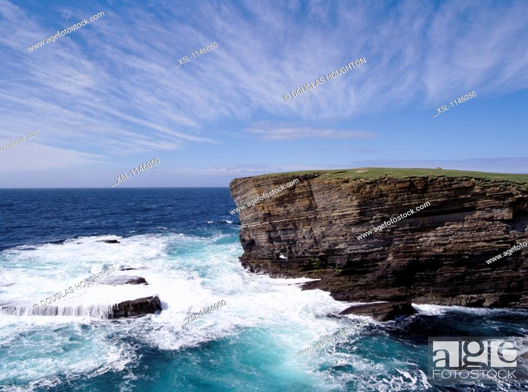 Stock Photo: Brough of Bigging YESNABY ORKNEY Sea waves rough seas blue sky cliffs coast.