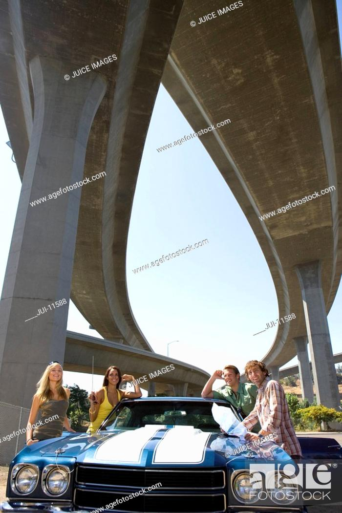 Stock Photo: Two young couples by car beneath overpass, smiling, portrait, low angle view.