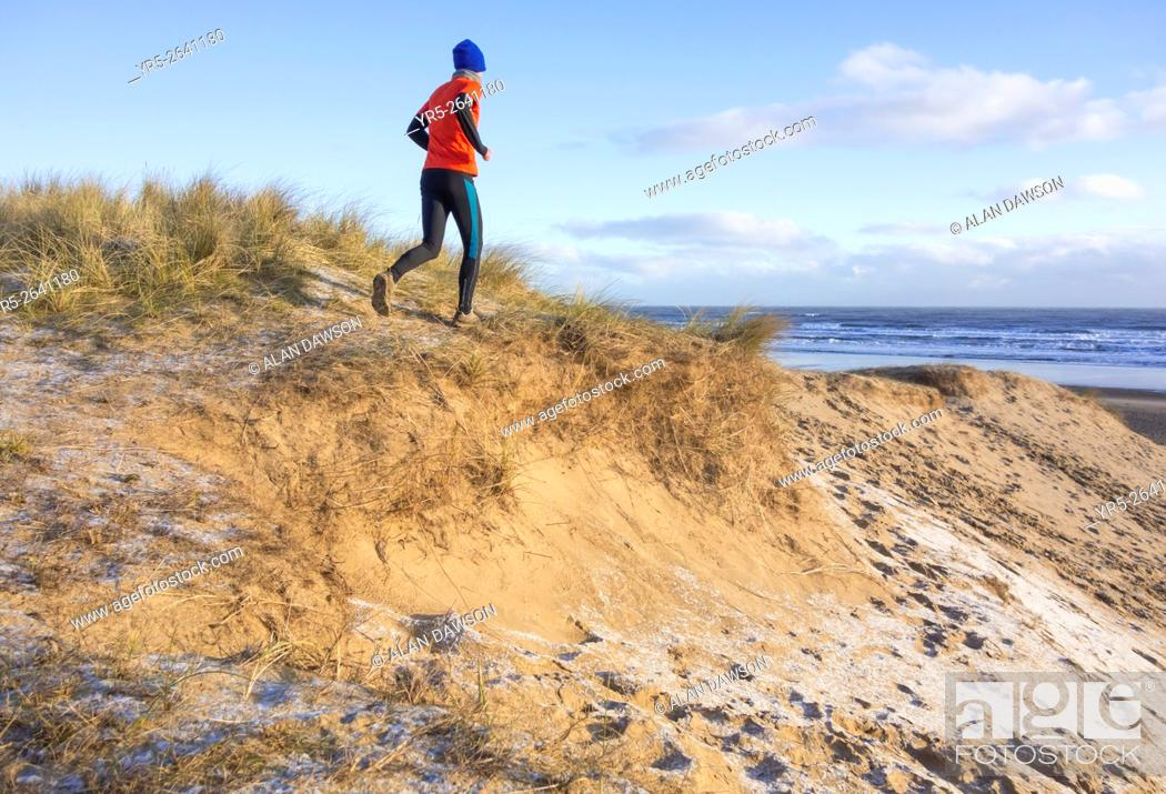 Stock Photo: Seaton Carew, north east England, United Kingdom, March 2016. Mature runner running on frost covered sand dunes on Seaton Carew beach at sunrise.