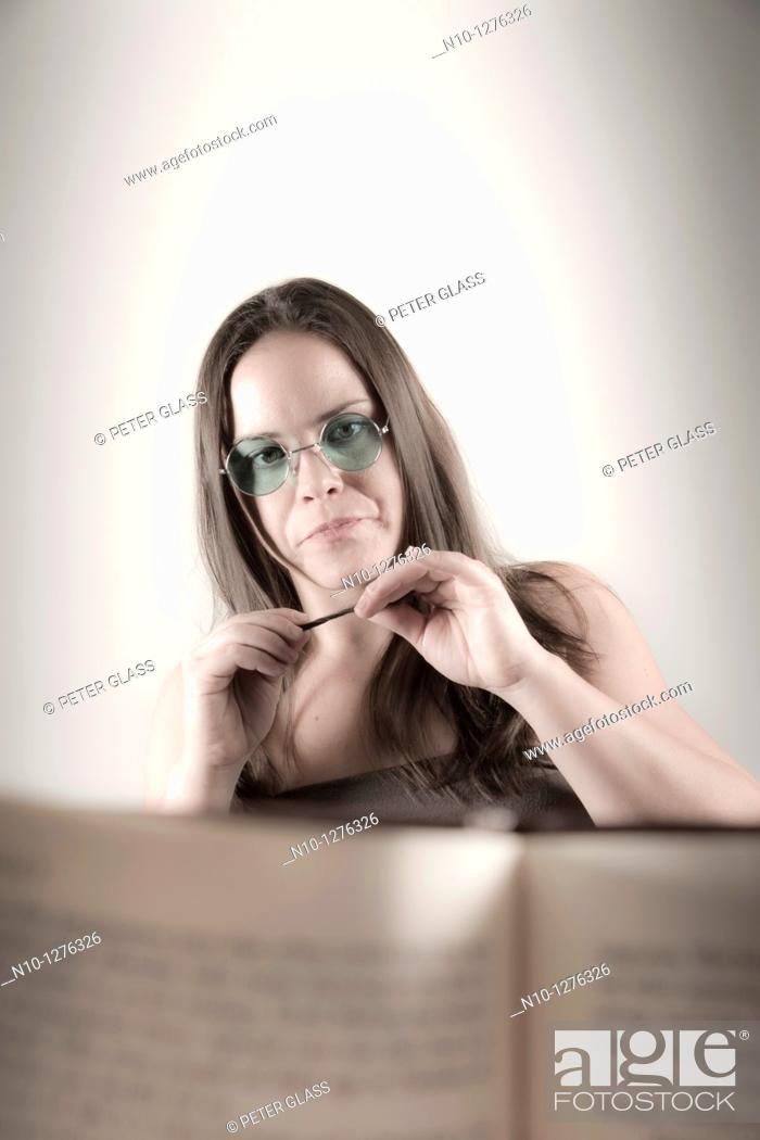 Stock Photo: Young woman seen from behind a book.