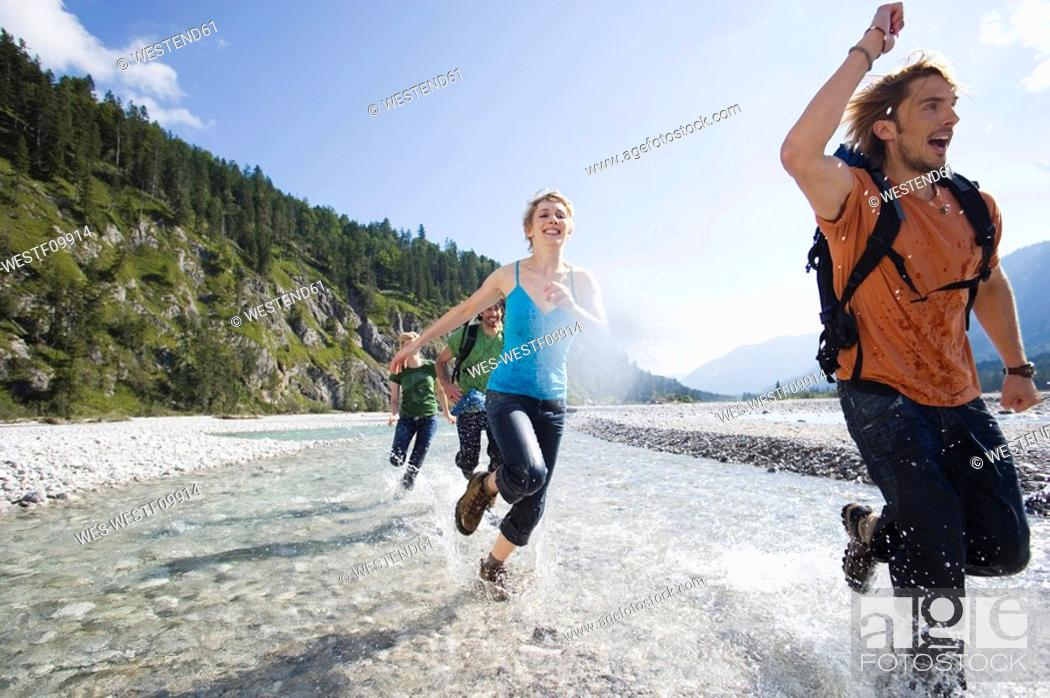 Stock Photo: Germany, Bavaria, Tölzer Land, Young friends running through river.