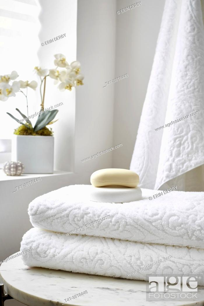 Stock Photo: A stack of white towels in a spa setting with soap and an orchid.