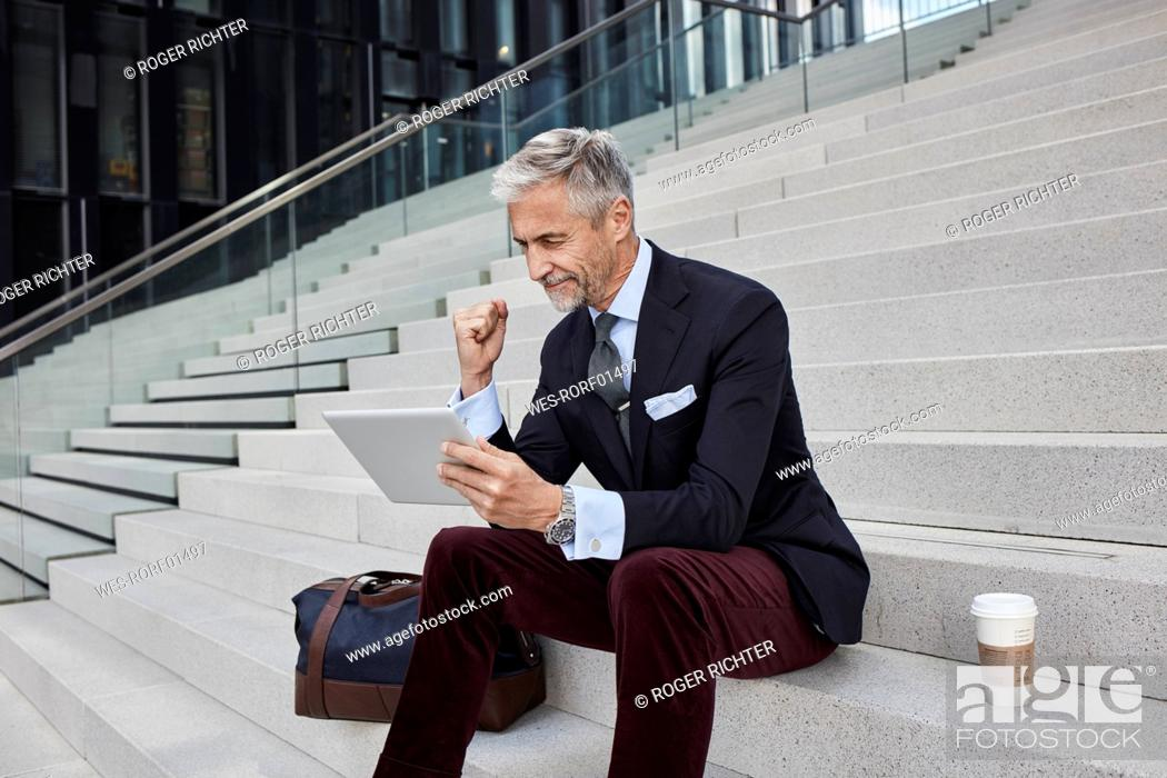 Stock Photo: Fashionable businessman with travelling bag nd coffee to go sitting on stairs using tablet.