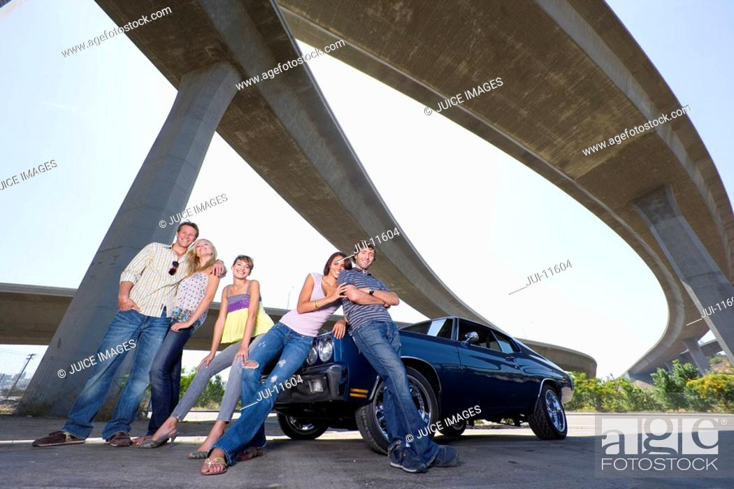 Stock Photo: Medium group of friends on bonnet of car beneath overpass, smiling, portrait, low angle view.