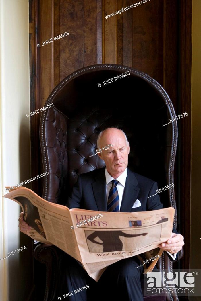 Stock Photo: Senior man reading newspaper in armchair.