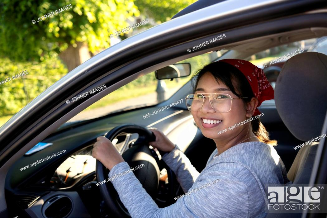Stock Photo: Smiling woman sitting in car.