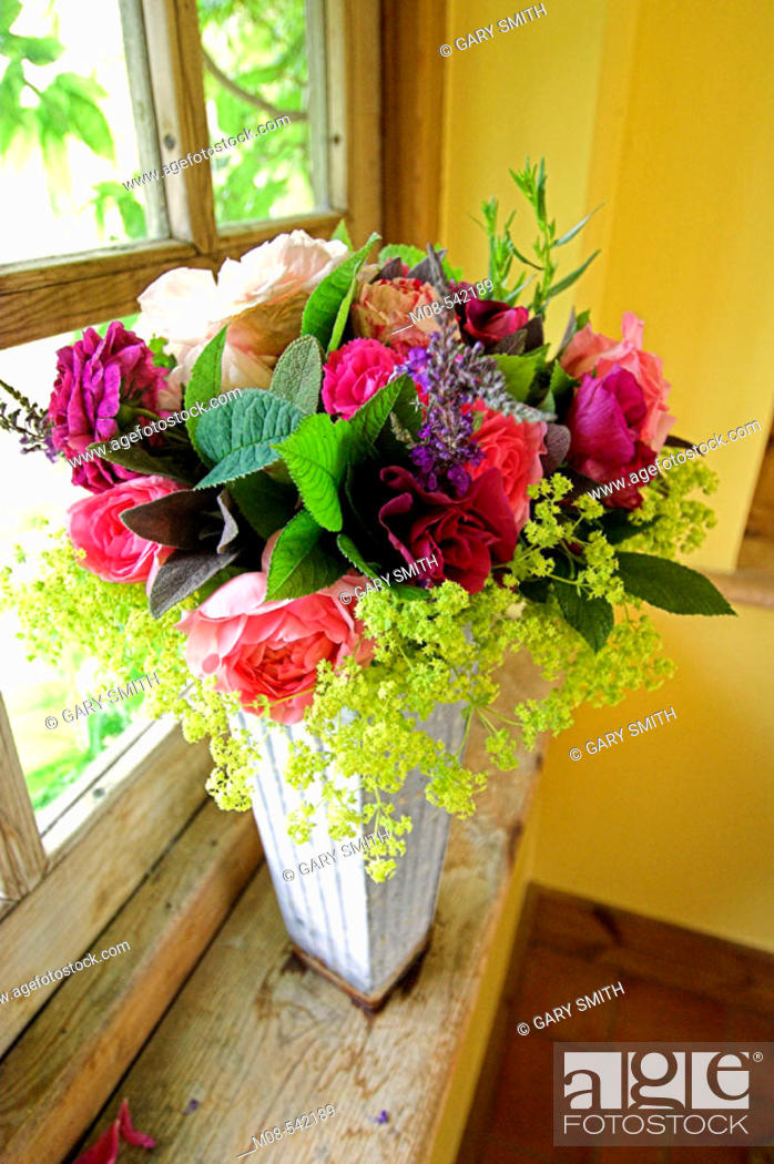 Stock Photo: Traditional summer vase of flowers including roses on a garden room windowsill.