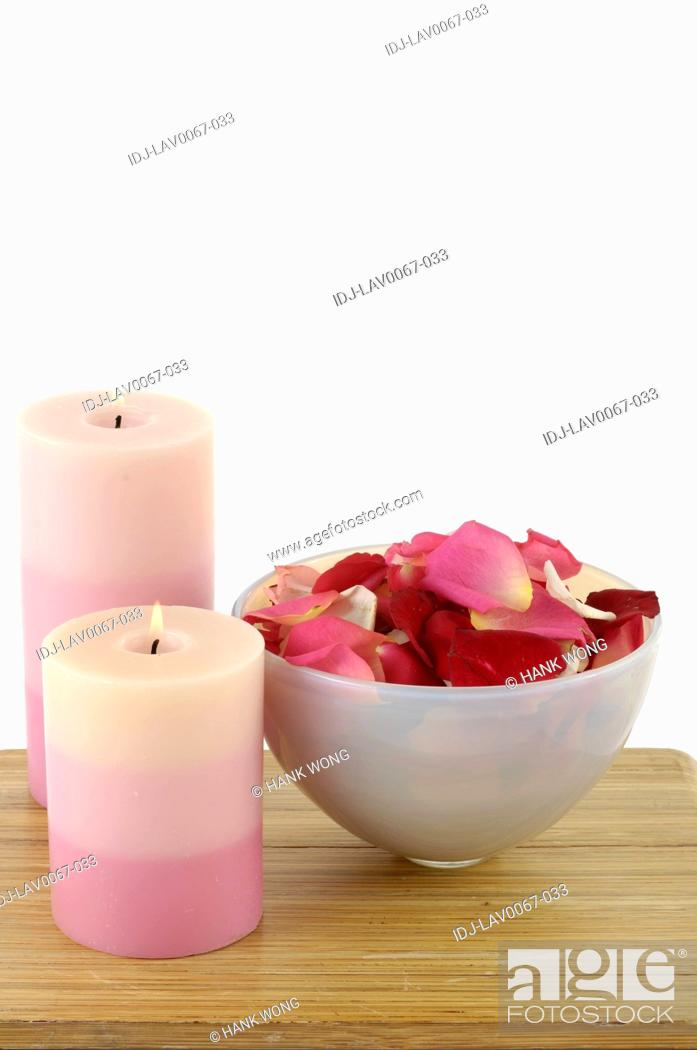 Stock Photo: Candles lit up near rose petals in a bowl.