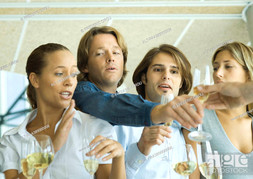 Stock Photo: Man reaching over friends' shoulders for glass of champagne.