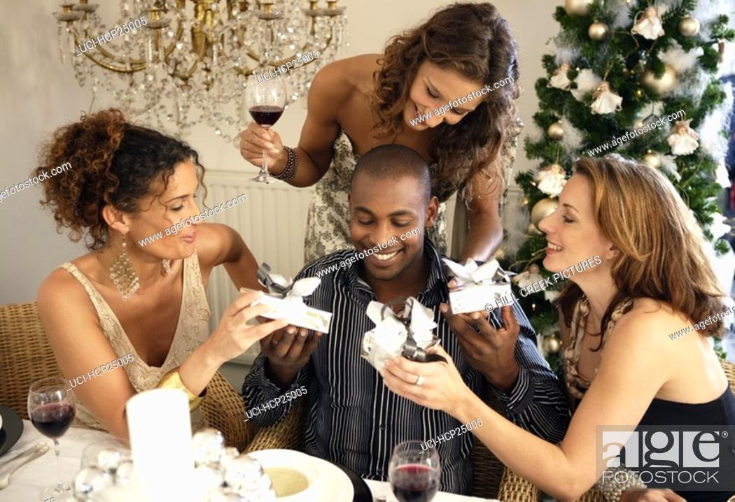 Stock Photo: People exchanging gifts at Christmas party.