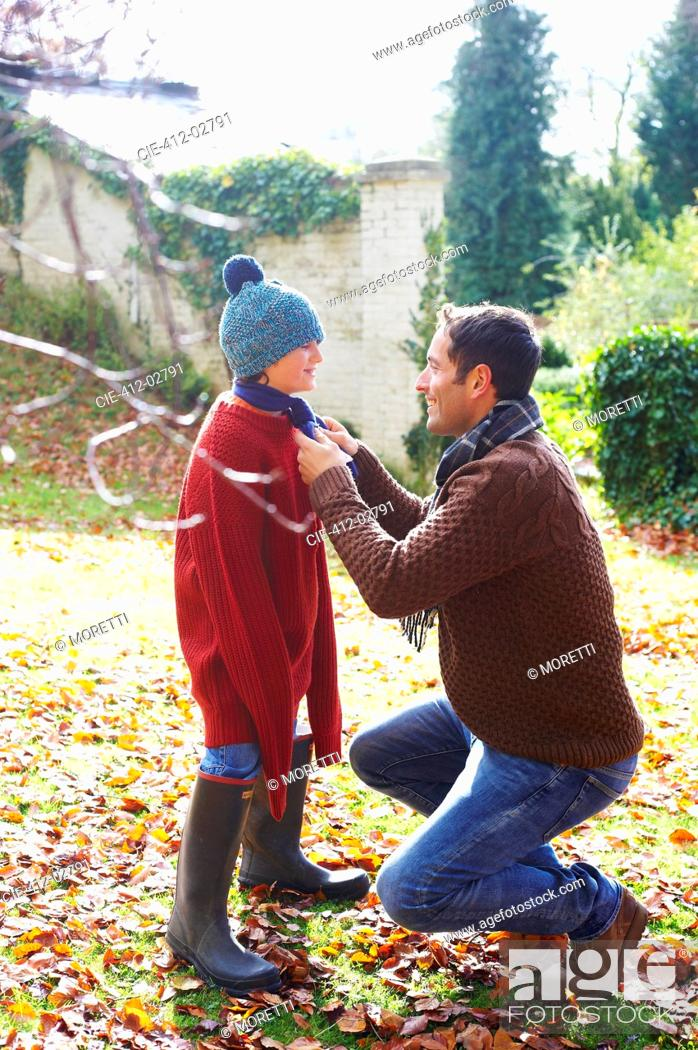 Stock Photo: Father tying son's scarf outdoors.