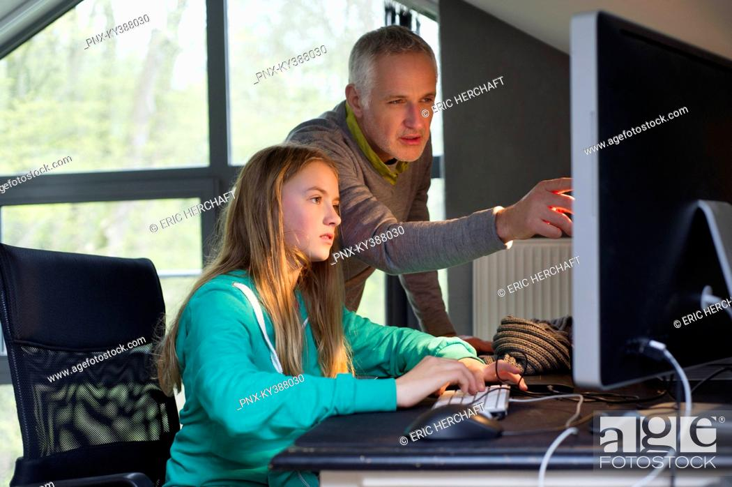 Stock Photo: Girl using a computer with her father at home.