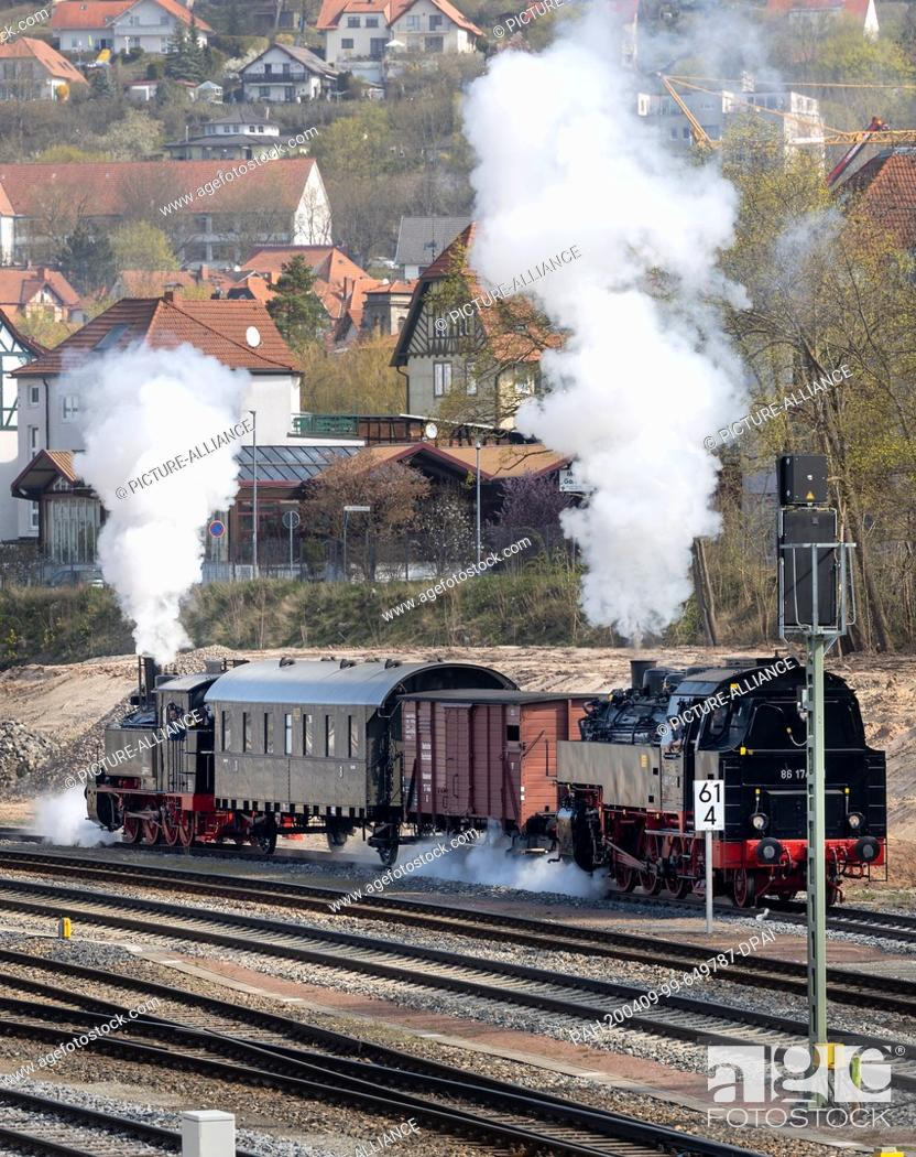 Stock Photo: 09 April 2020, Thuringia, Meiningen: The newly repaired steam locomotive 99 886 (l) of the Rhön train, which was severely damaged in an accident in the summer.
