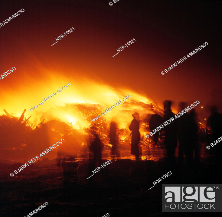 Stock Photo: People standing close to a bonfire on New Year's Eve.  Iceland, southwest, Gardabaer.