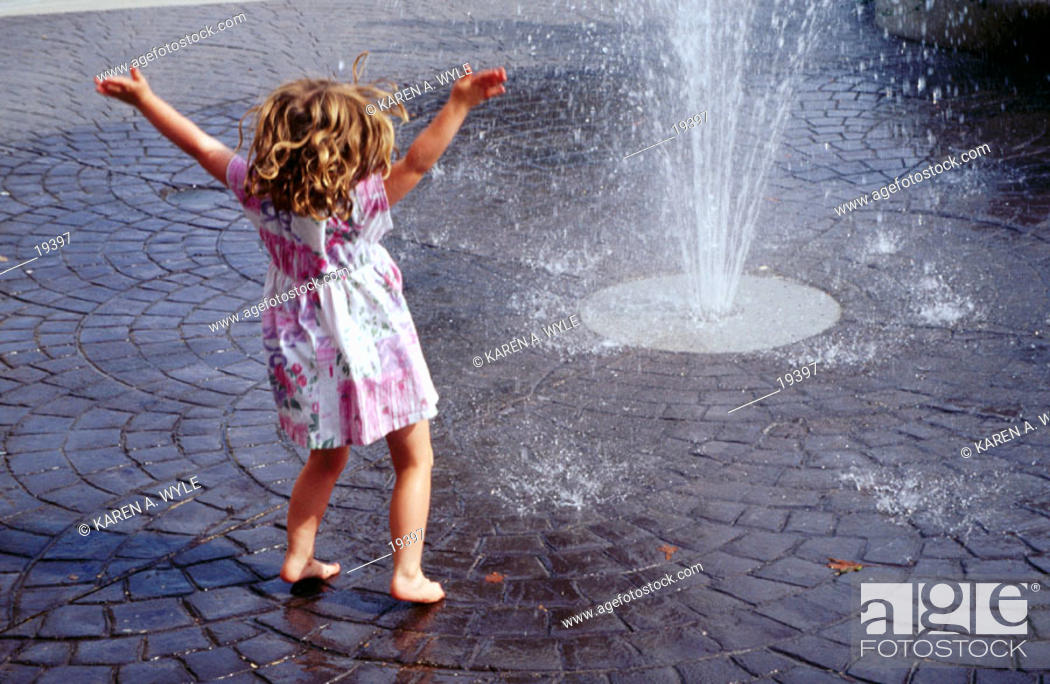 Stock Photo: Barefoot little girl with curly hair, in dress, arms wide, enjoying spray from street-level fountain.