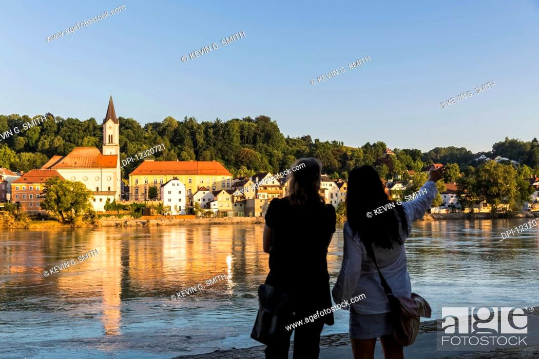 Photo de stock: Water reflects the Saint Gertrud Church on the river Inn, with two women standing and looking away from the camera in the foreground pointing downriver; North.