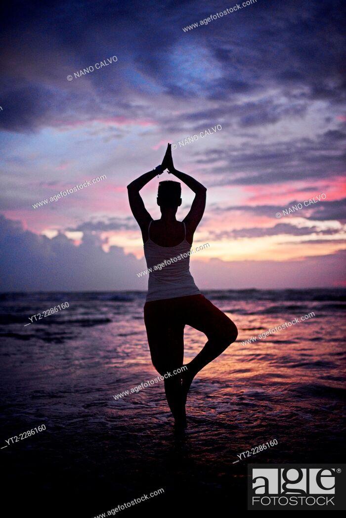 Stock Photo: Young woman doing yoga tree pose at sunset, Hikkaduwa beach, Sri Lanka.