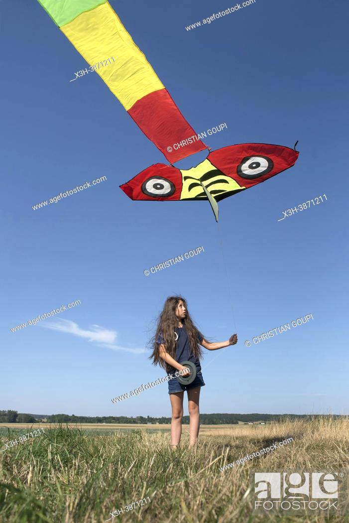 Photo de stock: Young girl in denim shorts and blue shirt flying a Chinese kite in a flat landscape in Centre-Val de Loire region, France.