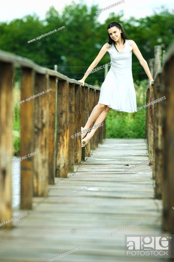 Photo de stock: Teen girl lifting self up on railing of wooden bridge, smiling at camera.