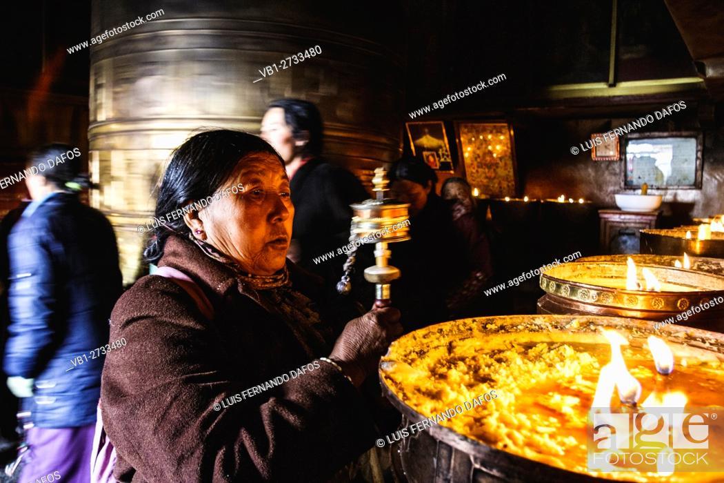 Stock Photo: Old Tibetan woman swinging prayer wheels at Mani Lhakhang chapel, Lhasa, Tibet.