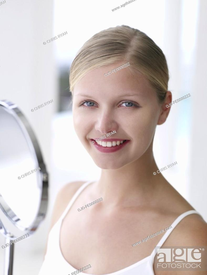 Stock Photo: Closeup of woman with mirror smiling.