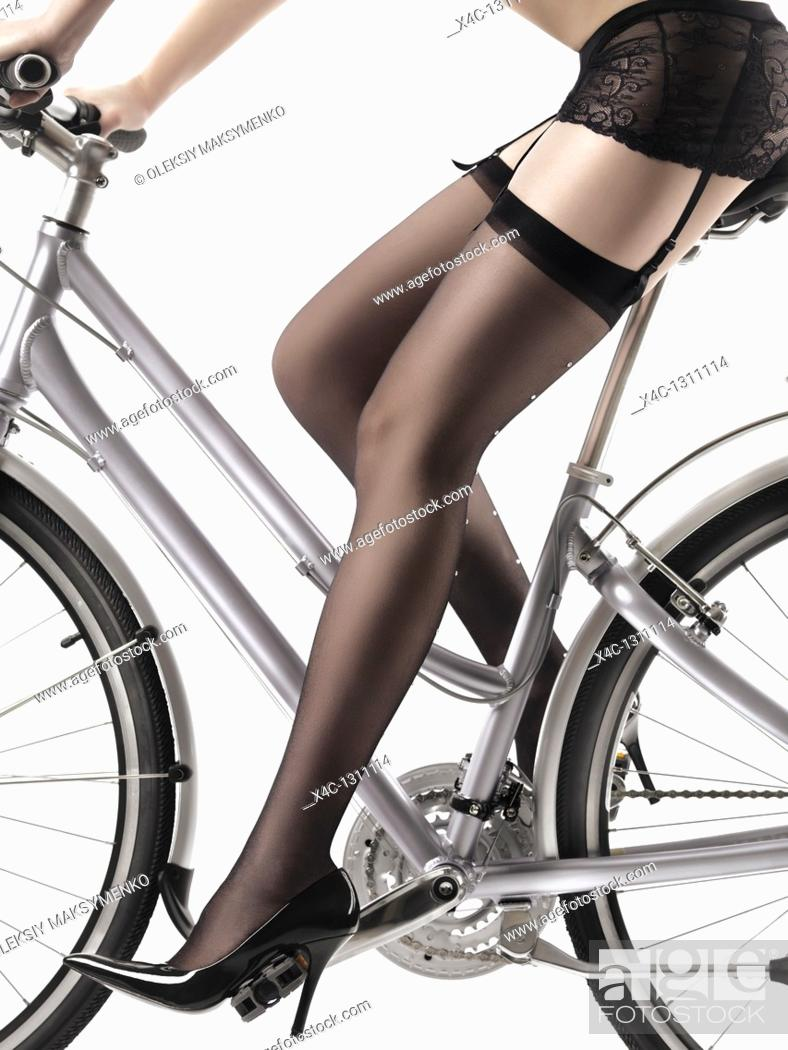 Stock Photo: Closeup of legs of a sexy woman wearing stockings and high heel shoes riding a bicycle.