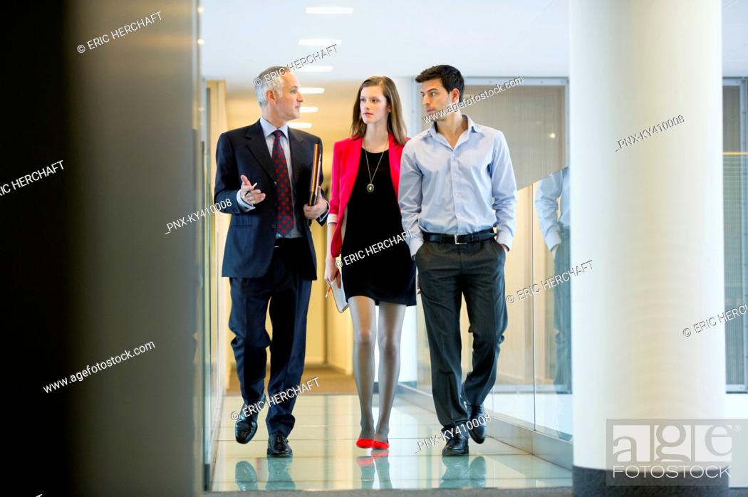 Stock Photo: Business executives discussing in an office corridor.