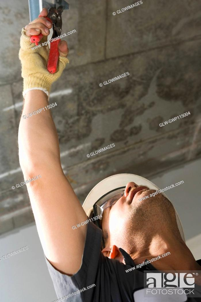 Stock Photo: Low angle view of a male construction worker working with pliers.
