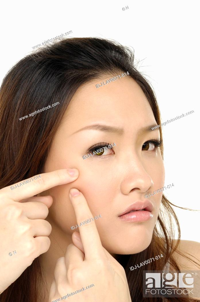 Stock Photo: Portrait of a woman squeezing spot.