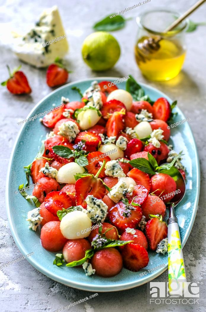 Stock Photo: Salad from watermelon, melon, strawberry, basil and blue cheese with honey.