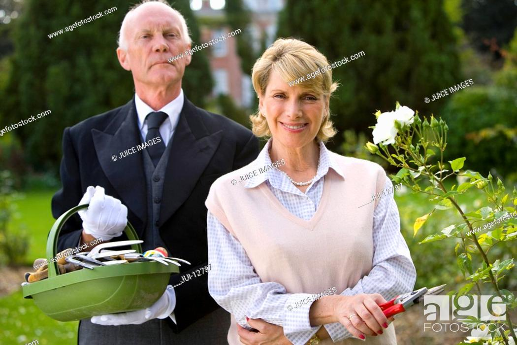 Stock Photo: Mature woman with secateurs by butler with basket of gardening tools, smiling, portrait.