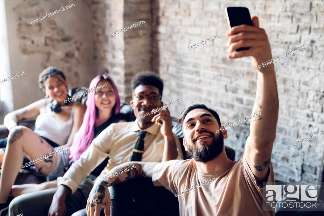 Stock Photo: Group of friends sitting on sofa in a lofttaking a selfie.