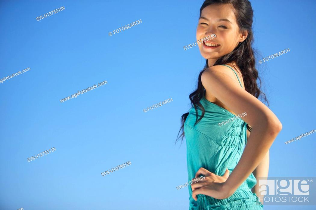 Stock Photo: Young Lady Standing, Hands on Hips, Smiling.