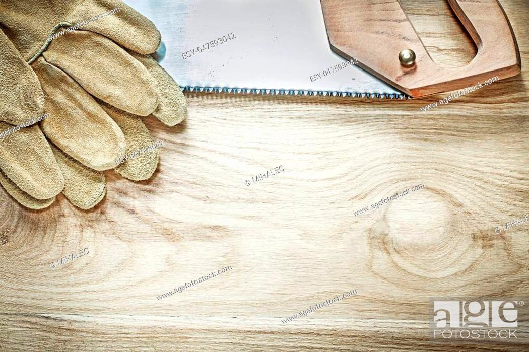 Stock Photo: Set of protective gloves stainless handsaw on wooden board construction concept.