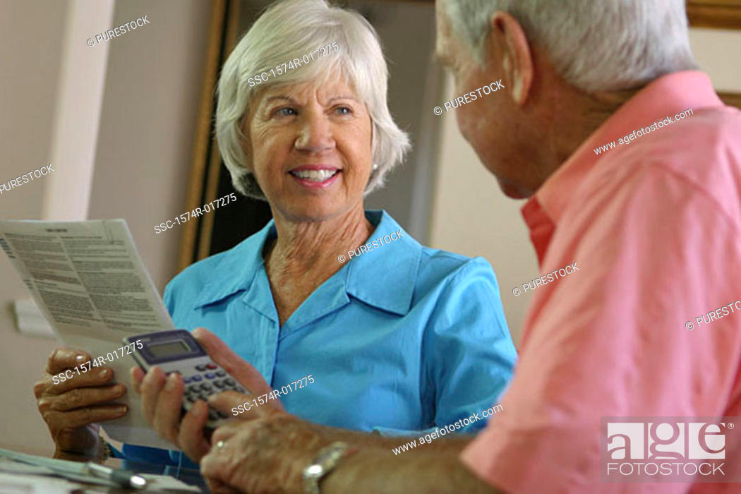 Stock Photo: Senior man using a calculator with a senior woman sitting beside him.