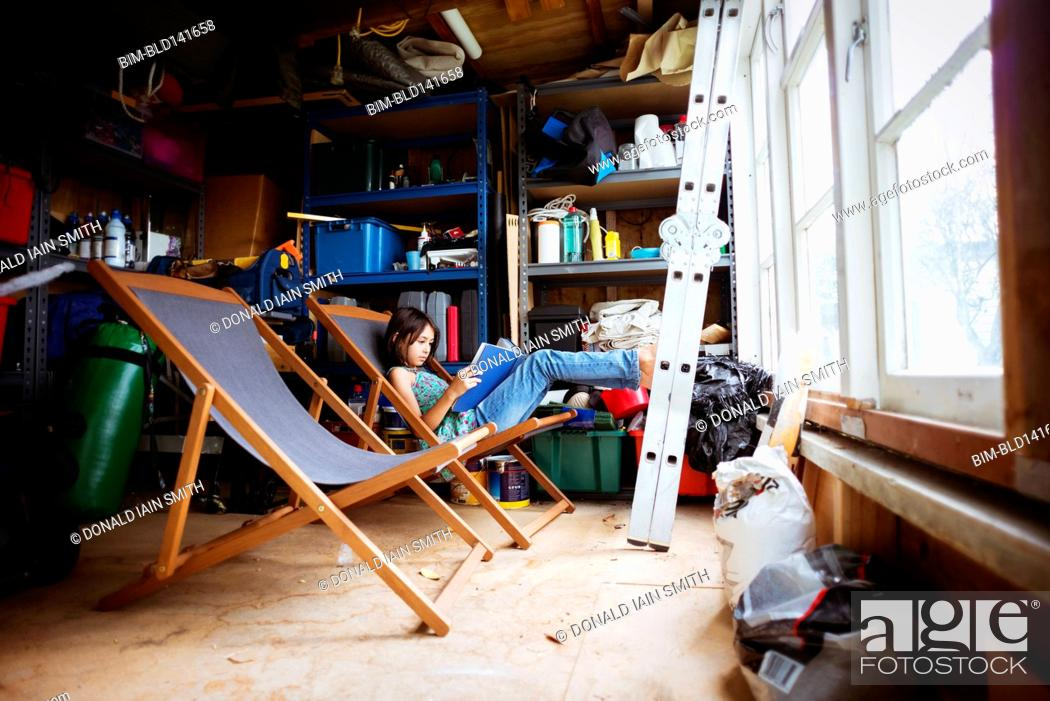 Stock Photo: Mixed race girl reading in lawn chair in shed.