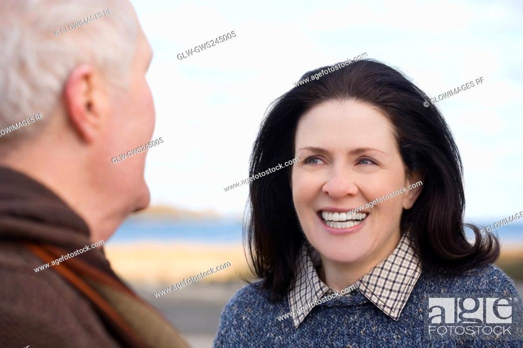 Stock Photo: Mature woman looking at a senior man and smiling.