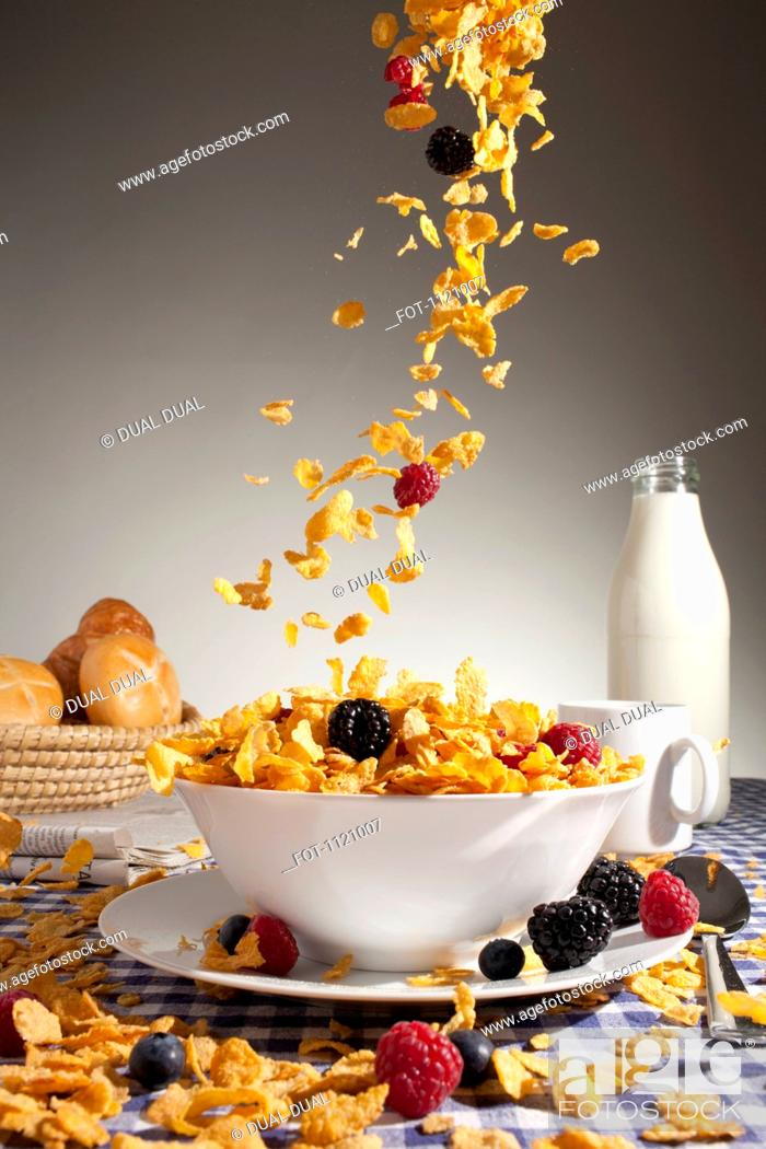 Stock Photo: Cereal and fruit being poured into a bowl.