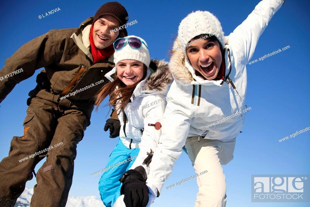 Stock Photo: Couple and daughter in ski wear smiling at camera.