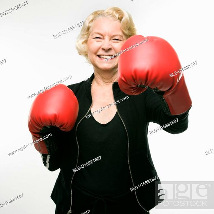 Stock Photo: Caucasian senior woman wearing boxing gloves and throwing punch at viewer.