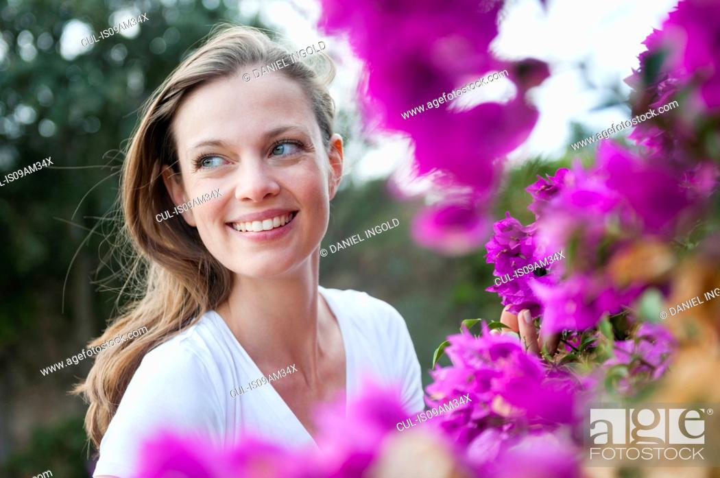 Stock Photo: Portrait of mid adult woman next to purple blossom, Sardinia, Italy.